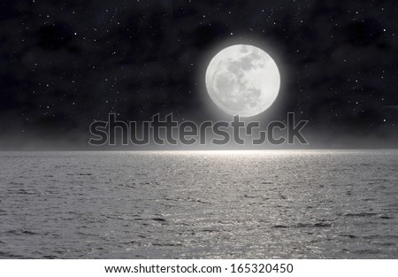 In the starry night the moon lights up the sea. - stock photo