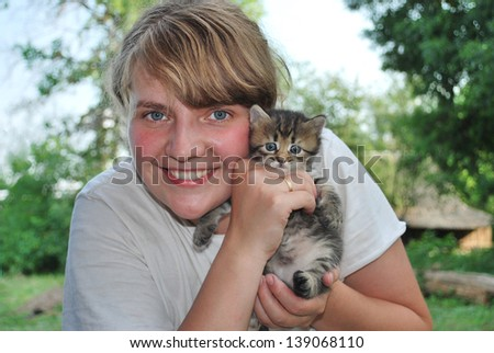 In the summer, cheerful smiling girl holding a kitten in her arms and cuddle - stock photo