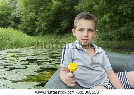 In the summer on the river a little serious boy sitting on a rubber boat and holding lily in hand. - stock photo