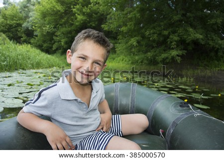 In the summer on the river curled happy laughing boy sitting on a rubber boat near water lilies. - stock photo