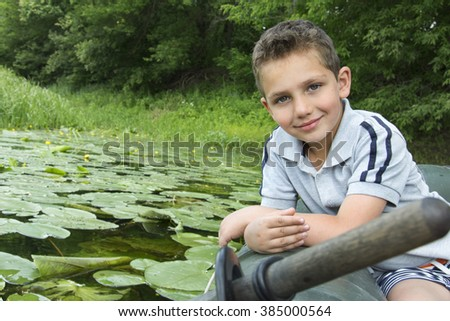In the summer on the river curly little boy sitting on a rubber boat near water lilies. - stock photo