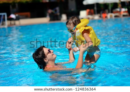 In the sunny day in the summer the boy in sun glasses and in a life jacket plays pool with mum - stock photo