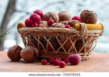 in the winter on the table a full basket of walnuts and red berries