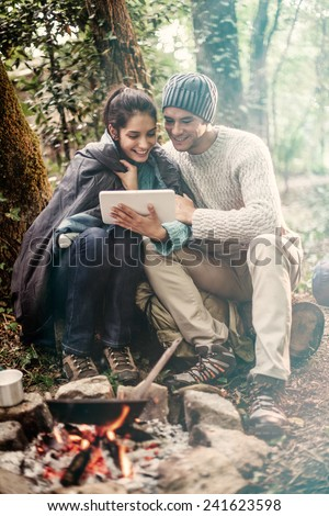 in the woods a couple sitting near a campfire using a digital tablet, she has a sleeping bag on the shoulders for warmth - stock photo