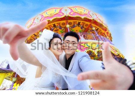 In this particular day we got married and this is a photo of us taken before the merry-go-round - stock photo