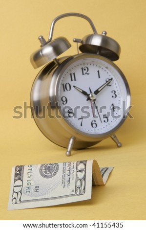 In today's world time is money.  Alarm clock and American paper currency isolated on a yellow background.