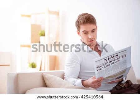 In touch with the world. Pleasant glad handsome man sitting on the couch and reading newspaper  while resting