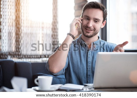 In touch with you. Cheerful handsome content smiling man sitting at the table and expressing gladness while talking on cell phone  - stock photo