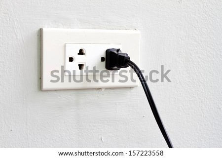 In use power socket on the white cement wall.