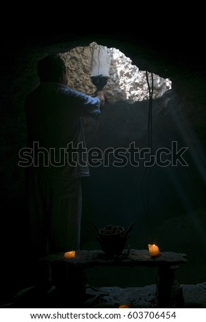 In white dressed hispanic priest performing a mayan purifying ritual inside a cave in low light penetrating the altar and being surrounded by a lot of smoke, creating a mystical atmosphere.