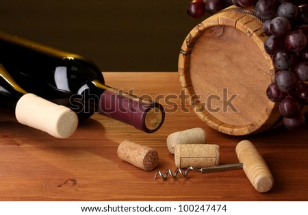In wine cellar. Composition of wine bottles and runlet - stock photo