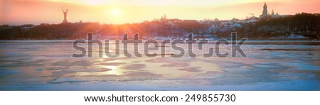 In winter, the largest river Dnieper Ukraine- chilling with ice, and at sunset the ancient walls of the Christian Orthodox monastery look beautiful, like many centuries ago in ancient history - stock photo