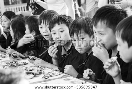 In Yen Bai, Vietnam - September 25th, 2015: Children ethnic minority people eat confectionery Tet moon on  afternoon in Yen Bai, Vietnam. Bread of love sharing of lives still lack something to eat.