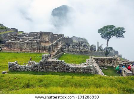 Inca city Machu Picchu in mist weather. It is a designated UNESCO World Heritage Site - Peru, South America - stock photo