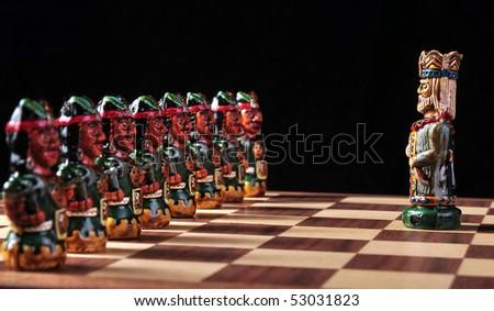 Inca pawns and Spaniard king of an ecuadorian chess set between Spaniards and Incas - stock photo