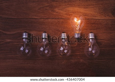 Incandescent lamps glowing on wooden background.  Concept for leadership. Concept for idea. Concept for solution. Concept for energy. - stock photo