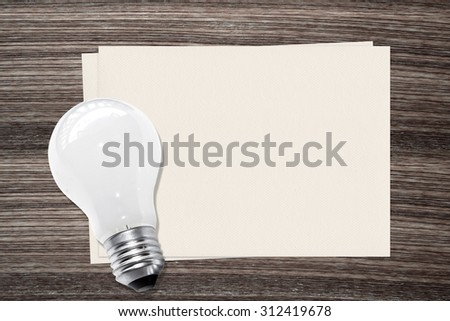 Incandescent light bulb and and paper on wood background - stock photo
