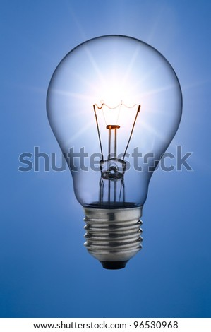 incandescent light bulb, on sunny skies background - stock photo