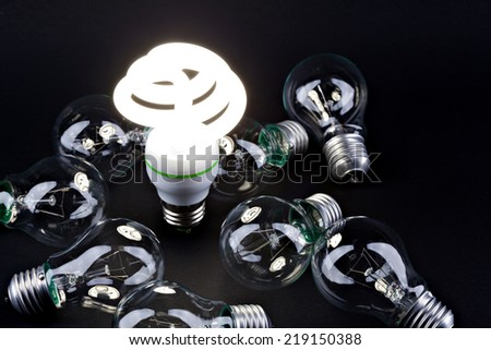 Incandescent light bulb with  fluorescent light bulb. Concept for energy conservation  - stock photo