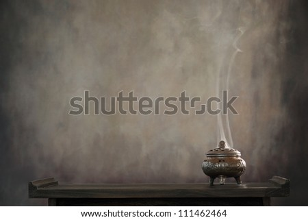 Incense burner on table, religious concept. - stock photo