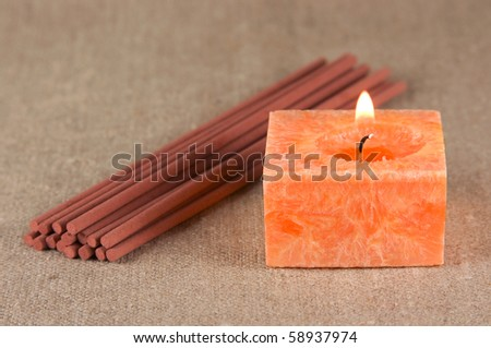 Incense sticks and orange burning candle on the fabric background - stock photo