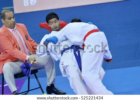 INCHEON, 03 October 2014: Looks referee almost hit when two athletes in action within karate during the 2014 Asian Games at Gyeyang Gymnasium, Incheon, Korea.