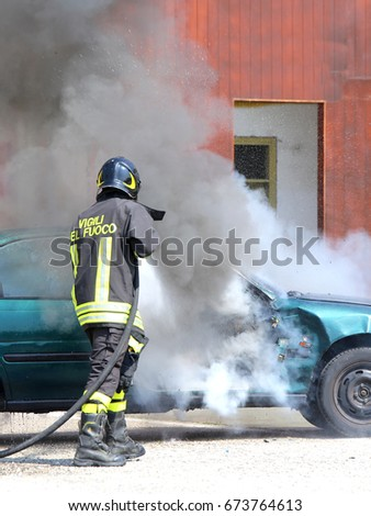 incident car with smoke and an Italian firefighter with the uniform with the written firefighters in the Italian language