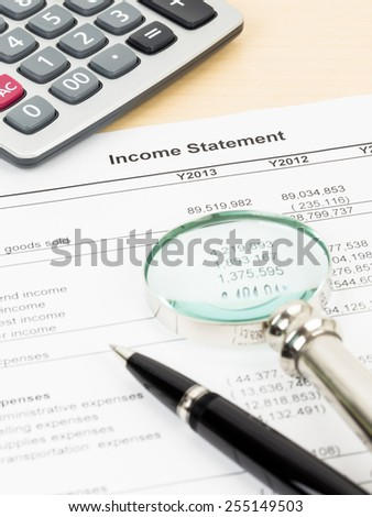 Income statement financial report with magnifier, pen, and calculator; document is mock-up
