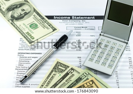 income statement report with calculator, pen and usd money for business - stock photo