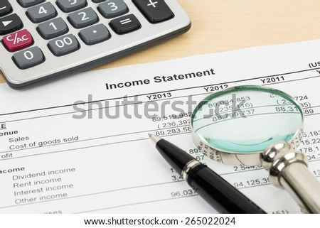 Income statement with pen, magnifier, and calculator; statement is mock-up