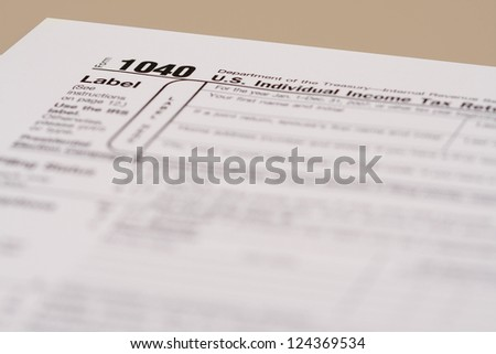 Income Tax Form 1040 with very shallow depth of field, on a beige desk.