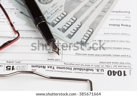 Income Tax Return Form with fountain pen and dollars