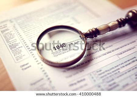 Income tax 1040 us individual tax return form and magnifying glass - stock photo