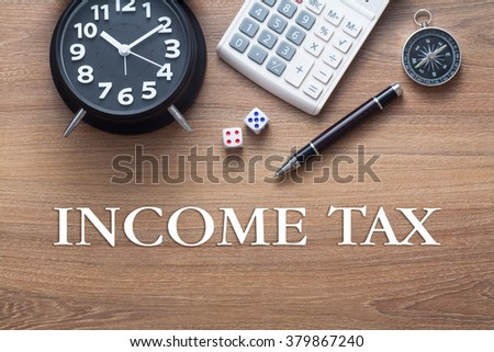 Income Tax words written on wooden table with clock,dice,calculator pen and compass - stock photo