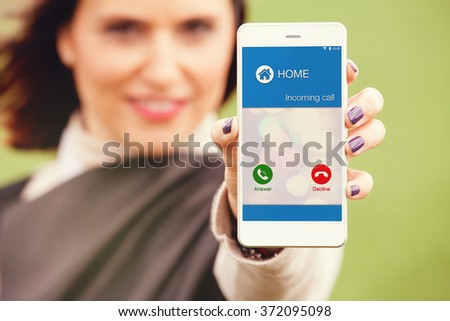 Incoming call from home on a mobile phone. Woman holding a mobile and showing the screen to the camera. - stock photo