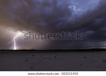incoming rain over the dry lake bed - stock photo