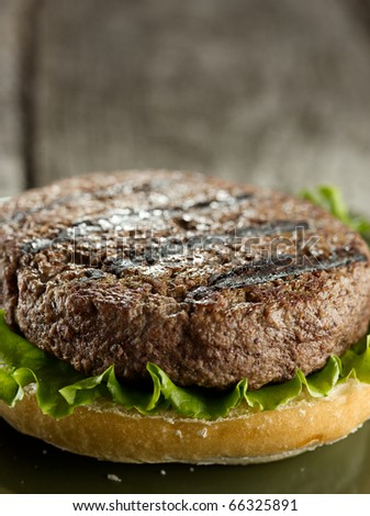 incomplete burger patty awaiting toppings  (note-selective focus) - stock photo