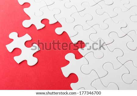 Incomplete puzzle with missing piece over red background - stock photo