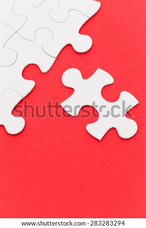 Incomplete white puzzle with red color background - stock photo
