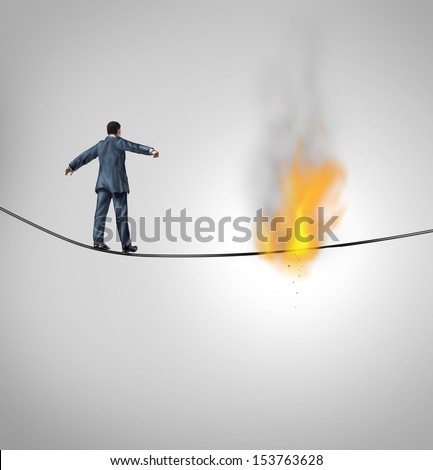 Increasing risk business concept and metaphor for overcoming adversity and dangers  following a risky strategy on the line as a businessman walking on a burning hazardous high wire thread. - stock photo