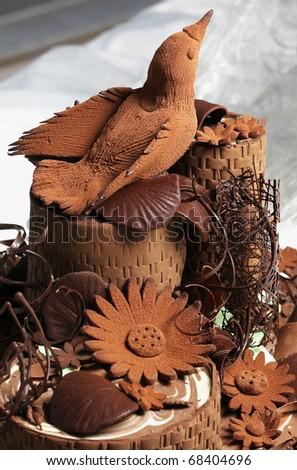 Incredible dessert art cocoa bird on top of chocolate cake - stock photo