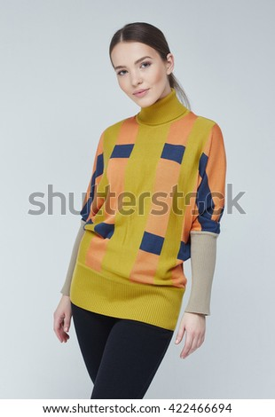 Incredible girl dressed in very attractive multi-coloured sweater