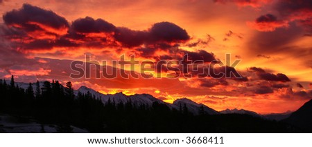 Incredible Mountain sunrise with dimly lit mountains in the foreground, full of colour - stock photo