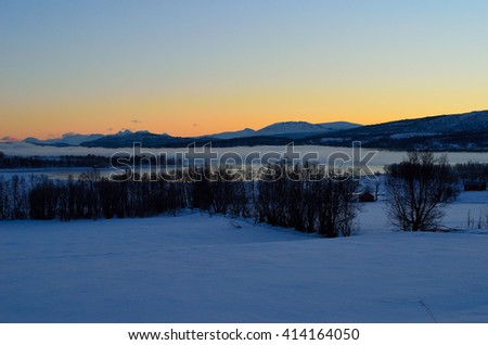 incredible thick frost smoke over cold fjord water at winter with colorful vibrant dawn sky over mountain peak - stock photo