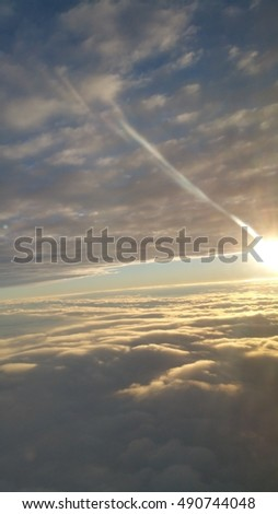 Incredible view above the clouds from an airplane of the sun shining on the clouds in the horizon.