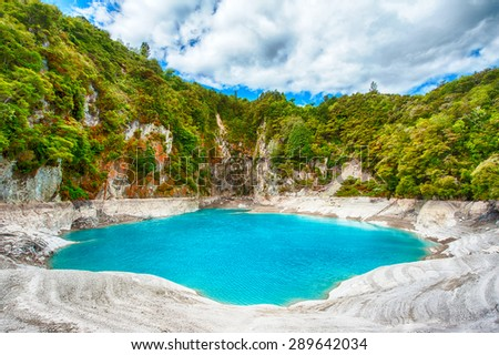 Incredibly blue and highly acidic Inferno Crater Lake at Waimangu geothermal area, New Zealand - stock photo