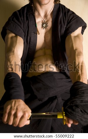 incredibly muscular body of a samurai warrior with katana or samurai sword in a kneeling pose - stock photo