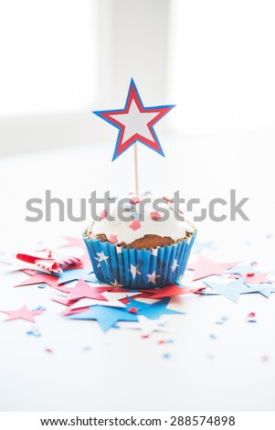 independence day, celebration, patriotism and holidays concept - close up of glazed cupcake or muffin decorated with star and cofetti on table at 4th july party - stock photo