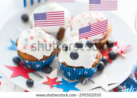 independence day, celebration, patriotism and holidays concept - close up of glazed cupcakes or muffins decorated with american flags and blueberries on plate at 4th july party - stock photo