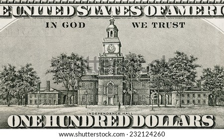 "Independence hall. Close-up of the text ""IN GOD WE TRUST"" American 100 dollar banknote revers - stock photo"